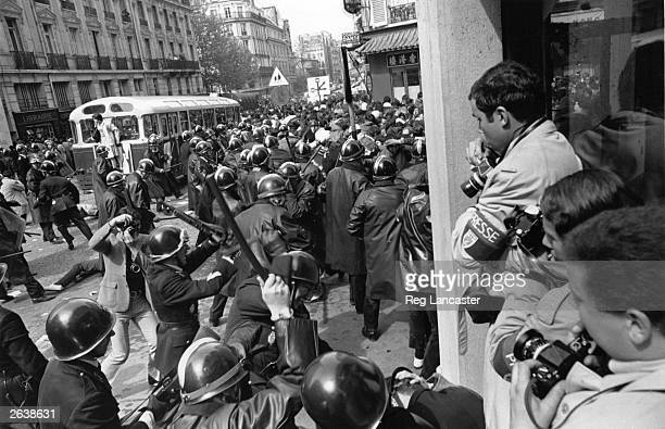 Press photographers huddle in a doorway as the police move into action on the streets of Paris during the 1968 student riots
