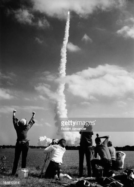 Press photographers photograph the launch of Space Shuttle Challenger at Kennedy Space Center in Florida The orbiter carried America's first female...