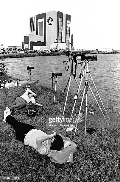 Press photographers rest while waiting for the launch of Space Shuttle Challenger at Kennedy Space Center in Florida the morning of its maiden launch...
