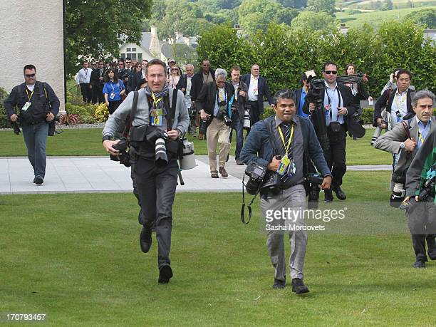 Press photographers run to the position of the leaders group photo at the G8 venue of Lough Erne on June 18 2013 in Enniskillen Northern Ireland The...