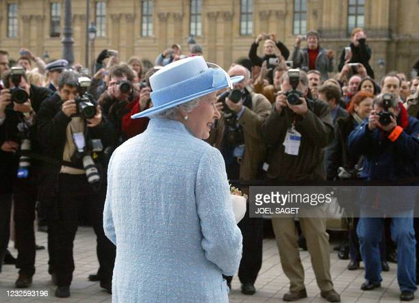 Press photographers snap pictures of Queen Elizabeth II outside the Louvre museum in Paris, where she viewed paintings which will form part of the...