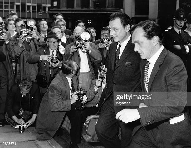 Press photographers surround Stephen Ward the society osteopath involved in the Profumo Affair as he arrives at the Old Bailey for the continuation...