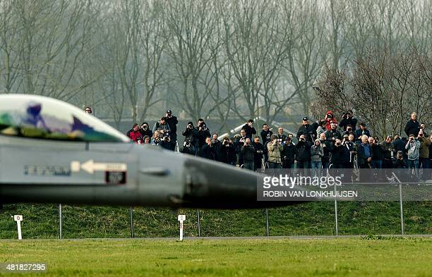Press photographers take pictures as ajet fighter aircraft rolls on the tarmac during the international exercise Frisian Flag 2014 at Leeuwarden...