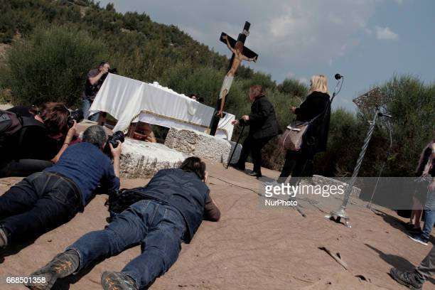 Press photographers take picutures while Orthodox Christians flock to worship the Crucified during the Apokathilosis a reenactment of the Deposition...