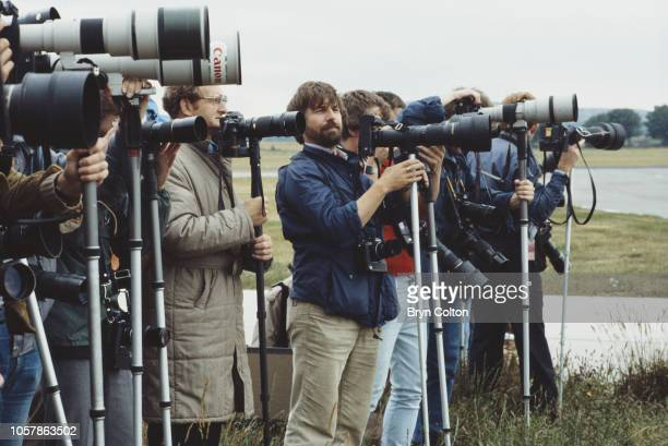 Press photographers with cameras and telephoto lenses stand on the tarmac at Aberdeen airport as they await the arrival of the Royal flight carrying...