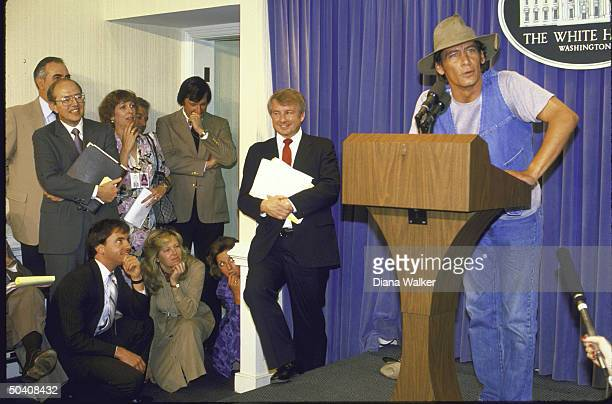 Press Secy Larry M Speakes and others watch Comic Actor Jim Varney in guise of character Ernest P Worrell giving surprise briefing at White House