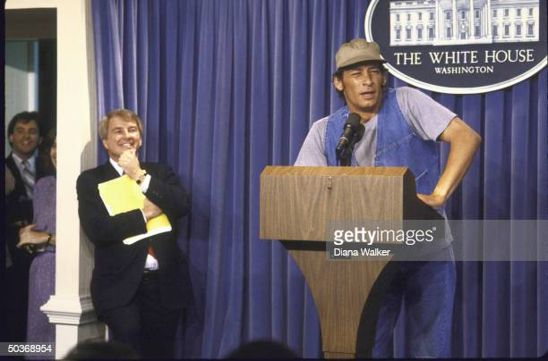 Press Secy Larry M Speakes laughing as Comic Actor Jim Varney in guise of character Ernest P Worrell gives surprise briefing at White House