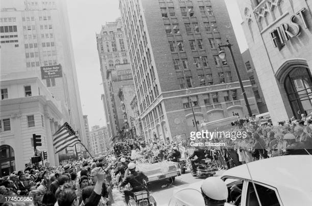 A press truck precedes Apollo 10 astronauts Gene Cernan Tom Stafford and John Young during a ticker tape parade in their honor along Montgomery...