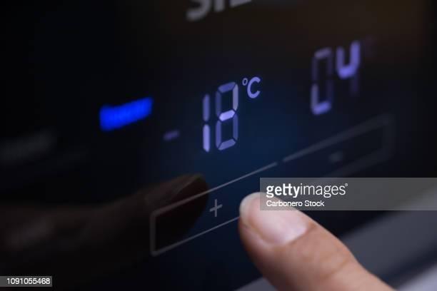 pressing fridge button - frío fotografías e imágenes de stock