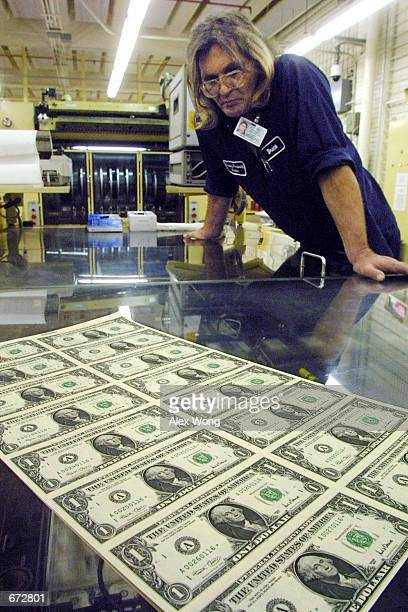 Pressman Bruce G Brzozowski inspects the printing process of the new Series 2001 onedollar bill notes which contains the signatures of US Treasury...