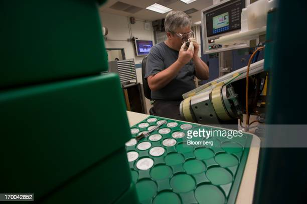 Pressman Larry Norton inspects a silver coin at the United States Mint at West Point in West Point New York US on Wednesday June 5 2013 Sales of gold...