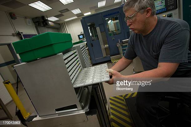 Pressman Larry Norton moves a rack of oneounce silver bullion coins at the United States Mint at West Point in West Point New York US on Wednesday...
