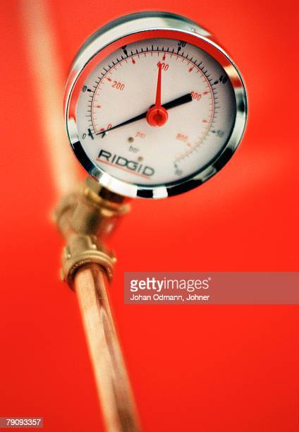 a pressure gauge against a red background. - pressure gauge stock photos and pictures