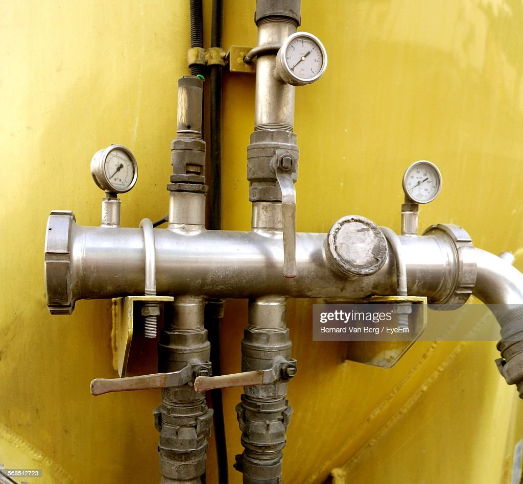 Pressure Gauge On Pipes Against Wall In Factory : Stock Photo
