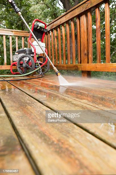 Pressure Washer Cleaning a Weathered Deck