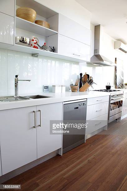 A prestige clean crisp white modern kitchen and wood floor