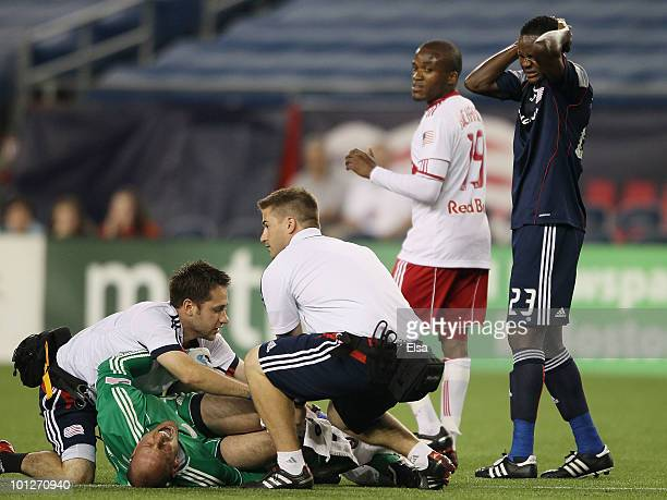 Preston Burpo of the New England Revolution is attended to by medical personnel as Joseph Niouky stands by after Burpo's leg was broken in the first...
