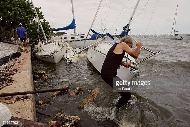 Preston Mclain and Bob Beck try and pull their boats off shore after they crashed ashore when Tropical Storm Alberto broke them from their moorings...