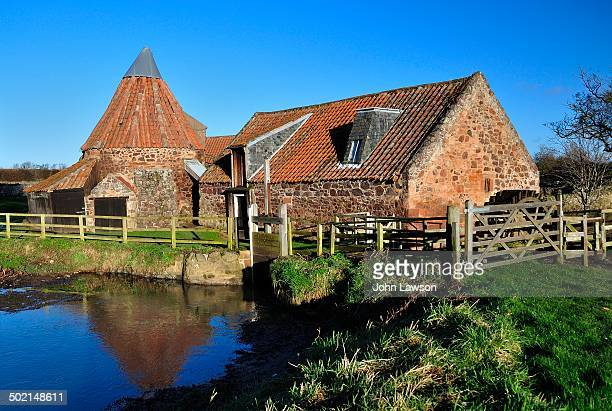 Preston Mill, East Linton, East Lothian, Scotland, pictured against a blue sky with the mill pond in the foreground.