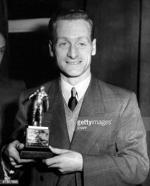 Preston North End's forward Tom Finney smiles as he holds his trophy 29 April 1954 in London after being elected the Footballer of the Year by the...