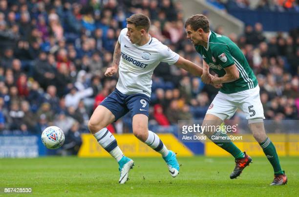Preston North End's Jordan Hugill holds off the challenge from Brentford's Andreas Bjelland during the Sky Bet Championship match between Preston...