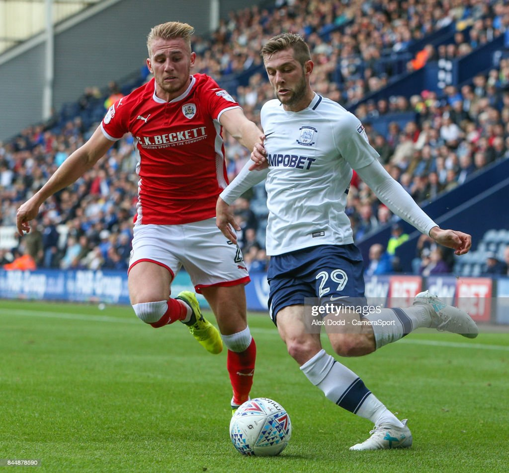 Preston North End's Tom Barkhuizen gets a cross in despite the attentions of Barnsley's Jason McCarthy during the Sky Bet Championship match between Preston North End and Barnsley at Deepdale on September 9, 2017 in Preston, England.
