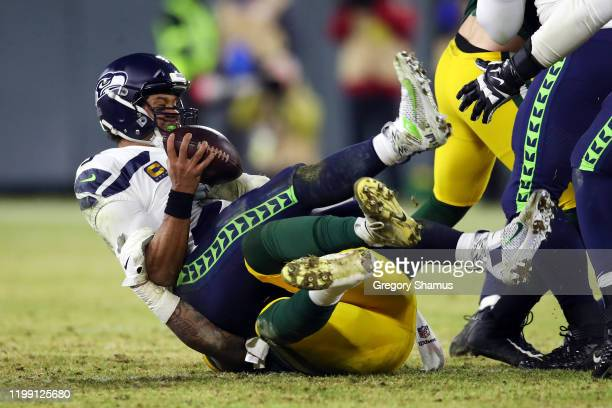 Preston Smith of the Green Bay Packers sacks Russell Wilson of the Seattle Seahawks during the fourth quarter in the NFC Divisional Playoff game at...