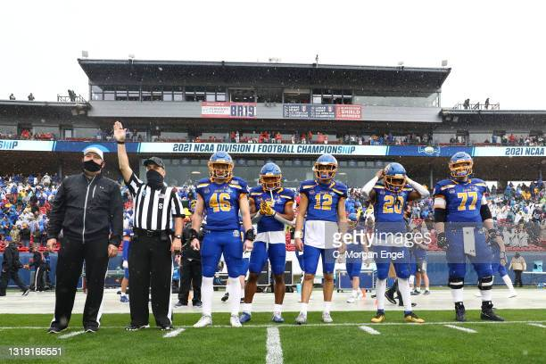 Preston Tetzlaff of the South Dakota State Jackrabbits prepares for the coin toss alongside Michael Griffin II and Logan Backhaus with Pierre Strong...