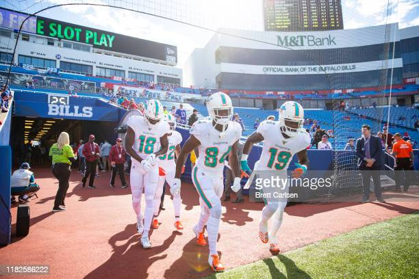 Preston Williams, Isaiah Ford and Jakeem Grant of the Miami Dolphins run onto the field to warm up before the game against the Buffalo Bills at New...