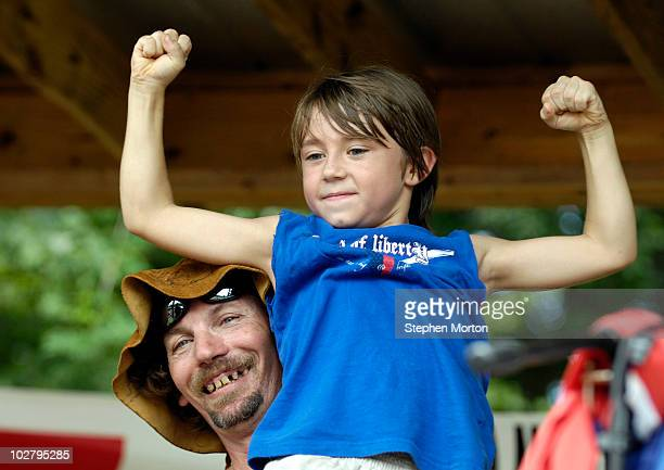 Preston Wright , the official mascot of the 14th Annual Summer Redneck Games, holds Armpit Serenade champion Aubrey Mathews after he clinched his...