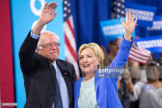 TOPSHOT Presumptive Democratic presidential candidate Hillary Clinton and Bernie Sanders waves after speaking at a rally in Portsmouth New Hampshire...