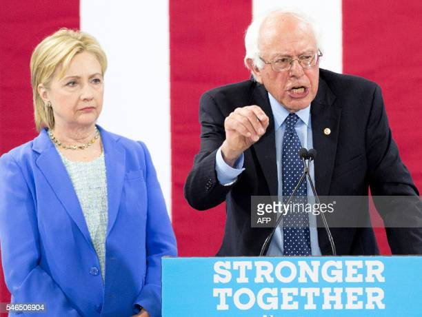 Presumptive Democratic presidential candidate Hillary Clinton listens as Bernie Sanders makes a point July 12 2016 at a rally in Portsmouth New...