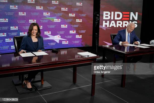 Presumptive Democratic presidential nominee former Vice President Joe Biden and his running mate Sen Kamala Harris sign required documents for...