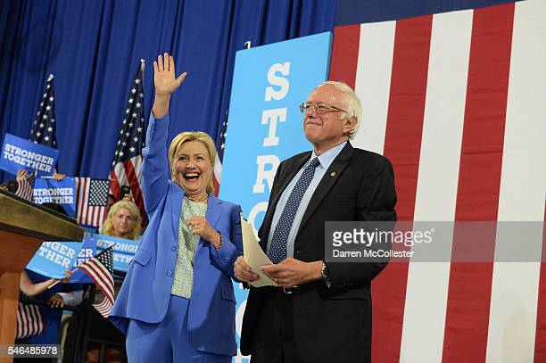 Presumptive Democratic presidential nominee Hillary Clinton and Bernie Sanders take the stage at Portsmouth High School July 12 2016 in Portsmouth...