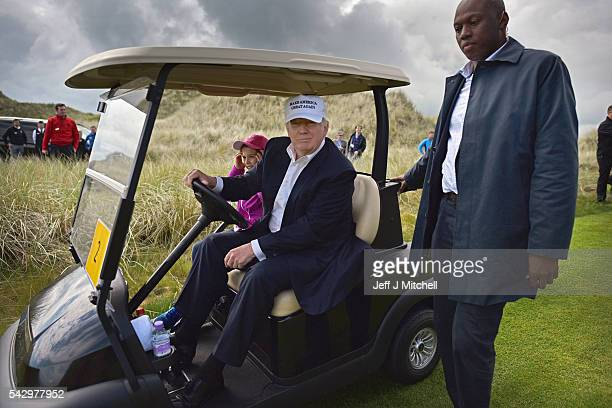 Presumptive Republican nominee for US president Donald Trump and his granddaughter Kai visit Trump International Golf Links on June 25 2016 in...