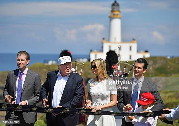Presumptive Republican nominee for US president Donald Trump cuts a ribbon on the 9th tee at his Trump Turnberry Resort surrounded by his family Eric...
