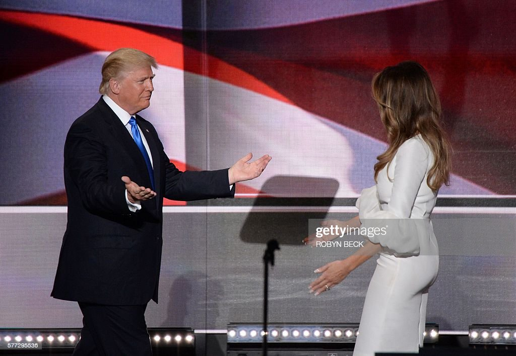 TOPSHOT - Presumptive Republican presidential candidate Donald Trump greets his wife Melania Trump following her address to delegates on the first day of the Republican National Convention on July 18, 2016 at Quicken Loans Arena in Cleveland, Ohio. The Republican Party opened its national convention, kicking off a four-day political jamboree that will anoint billionaire Donald Trump as its presidential nominee. / AFP / Robyn BECK