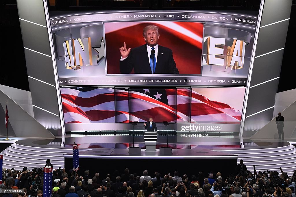 TOPSHOT - Presumptive Republican presidential candidate Donald Trump introduces his wife Melania Trump (out of frame) to delegates on the first day of the Republican National Convention on July 18, 2016 at Quicken Loans Arena in Cleveland, Ohio. The Republican Party opened its national convention, kicking off a four-day political jamboree that will anoint billionaire Donald Trump as its presidential nominee. / AFP / Robyn BECK