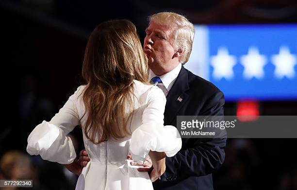 Presumptive Republican presidential nominee Donald Trump kisses his wife Melania before she delivers a speech on the first day of the Republican...