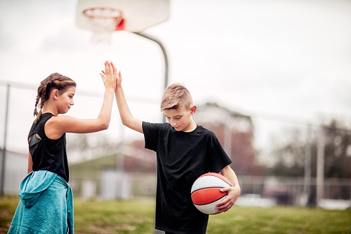 pre-teen boy and girl giving each other a high-five after basketball game - gettyimageskorea