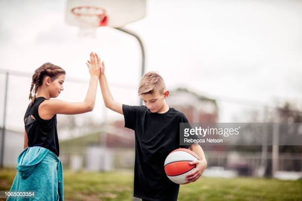 pre-teen boy and girl giving each other a high-five after basketball game - basketball sport stock pictures, royalty-free photos & images