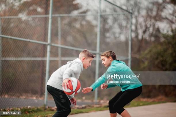 pre-teen boy and girl playing basketball on the playground