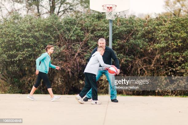 pre-teen boy and girl playing basketball on the playground with their father