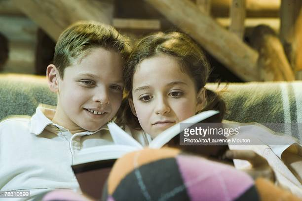Preteen boy and girl reading book together