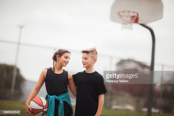 pre-teen boy and girl with arms around each other on playground after basketball game