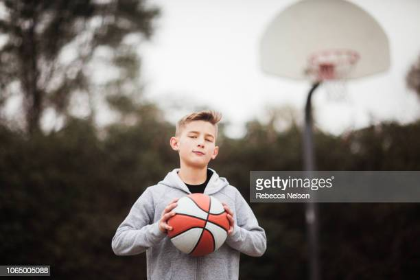 pre-teen boy holding a basketball on playground