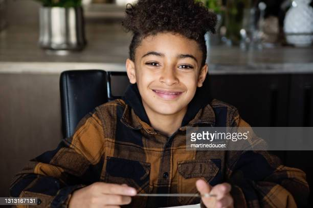 """preteen boy homeschooling on the dining room table. - """"martine doucet"""" or martinedoucet stock pictures, royalty-free photos & images"""