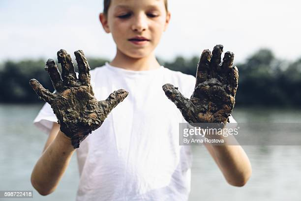 Preteen boy in white t-shirt with muddy hands on river bank