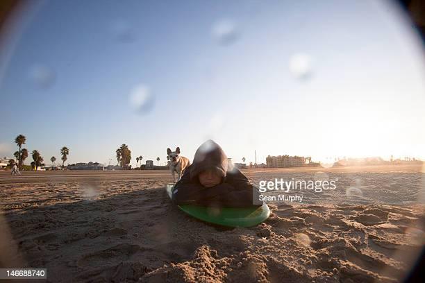 Pre-Teen Boy laying on Surfboard