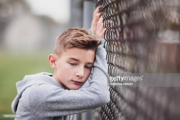 pre-teen boy leaning against chainlink fence on playground